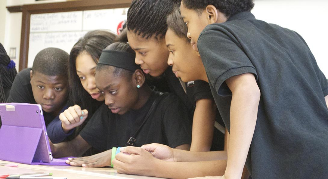 A group of Black students are standing and sitting around a desk, with an iPad on the desk.  All are viewing content on the iPad screen, as part of an activity in which they are playing charades based on clues on medical conditions.