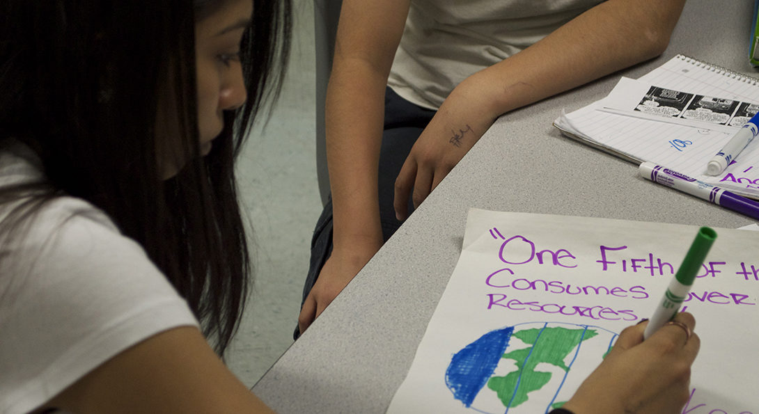 A Latina student sits at a desk and is writing on a poster with a green marker, coloring in an illustration of the planet Earth.  The poster features text about consumption of resources on the planet.