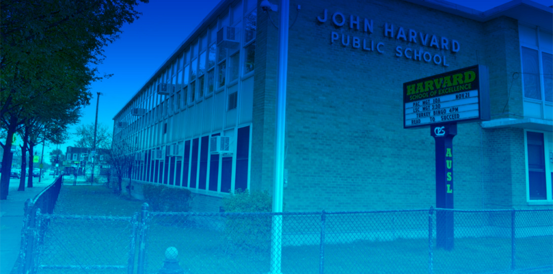 The exterior of John Harvard Elementary School, a Chicago Public School, shown from a street corner, with a row of trees to the left of the school lining the sidewalk.