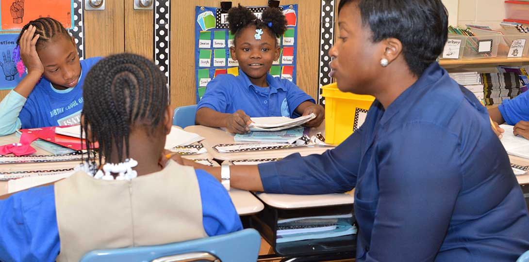 Principal Peggie Burnett is observing a classroom, sitting at a desk momentarily to talk with three Black students about what they are working on.