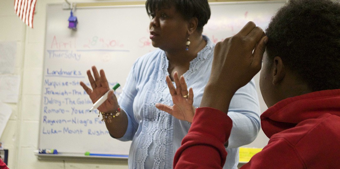 Teacher Debra Thomas gesticulates to a group of special education students in her classroom, holding a whiteboard marker in her right hand.  A Black male student is sitting and listening to her to her left.