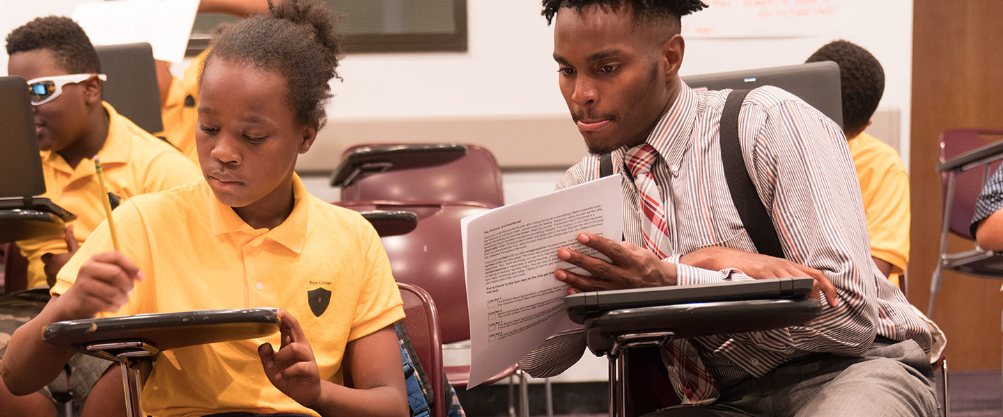 Doctoral student Durrell Jamerson-Barnes sits at a desk next to a student.  He is holding a piece of paper in his hand and is pointing to text on the paper, while the student to his right is writing on a piece of paper with a pencil.