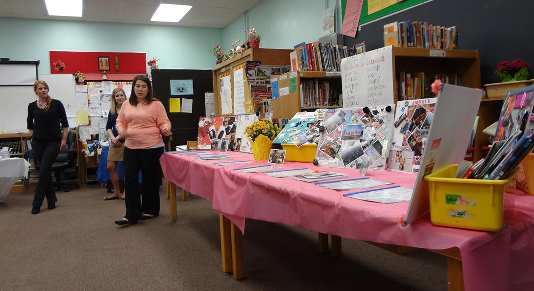 A woman stands to the left of two long tables covered in pink tableclothes.  On the tables are examples of culturally relevant literature for Latina girls.