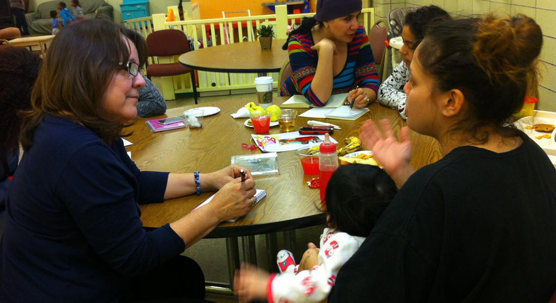 Professor Norma Lopez-Reyna sits next to a mother holding a baby in her lap at a table.  Lopez-Reyna is taking notes on a life story from the woman, who is gesturing with her right hand.  Other pairs of women sit at the table in the background, engaged in the same writing activity.