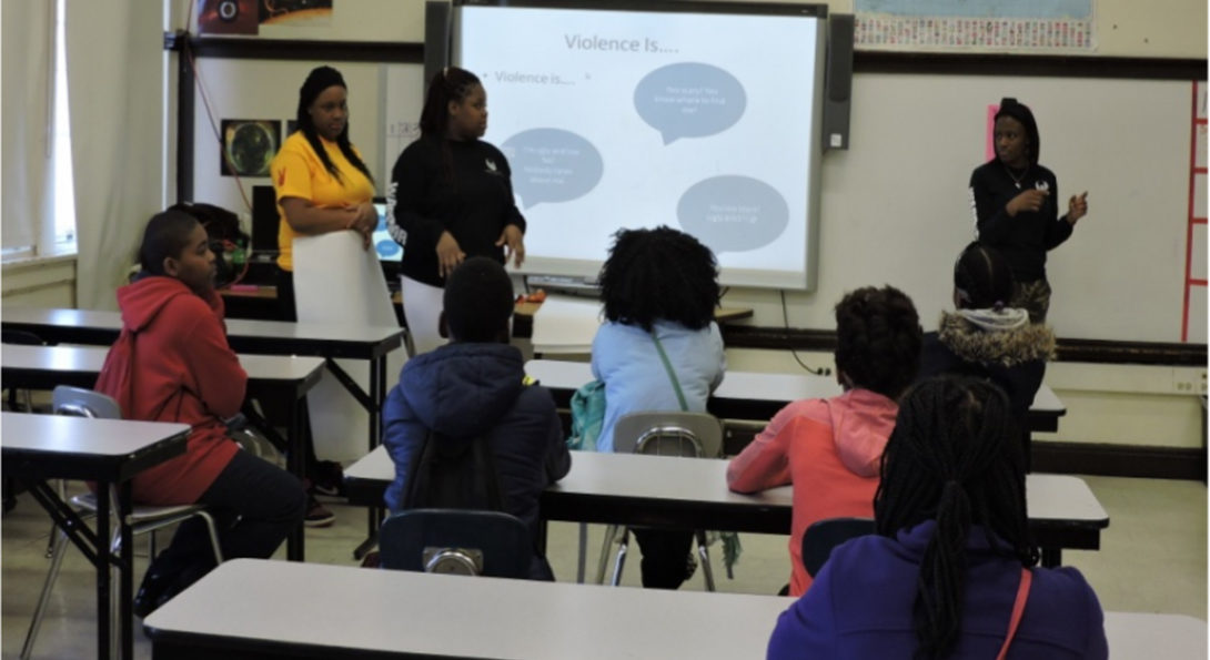 At North Lawndale College Prep, three Black girls lead a workshop on non-violent conflict resolution for their peers.  They are standing at the front of a classroom, with a projection screen pulled down and their presentation projected on it.  In the foreground, their peers sit at desks, listening to the presentation.