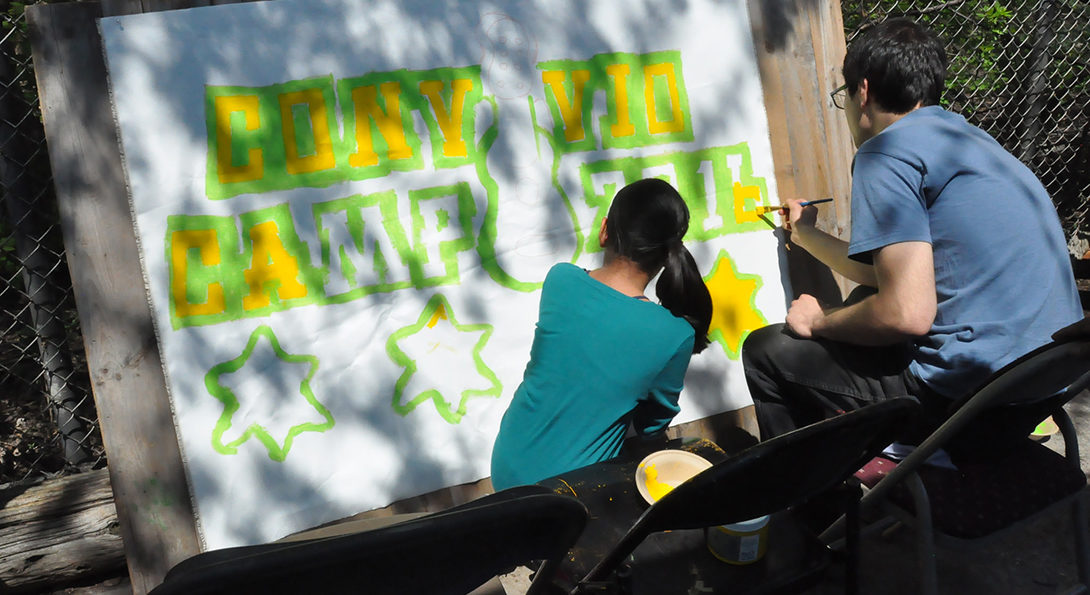 A man and a woman are sitting and crouching and painting a large white sign with yellow and green paint.