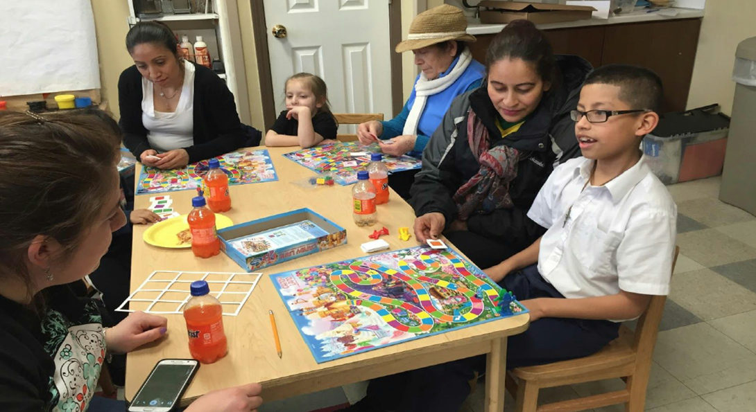 A woman is working with a child on a puzzle, seated at a table with other parents and children, at a workshop in Pilsen.
