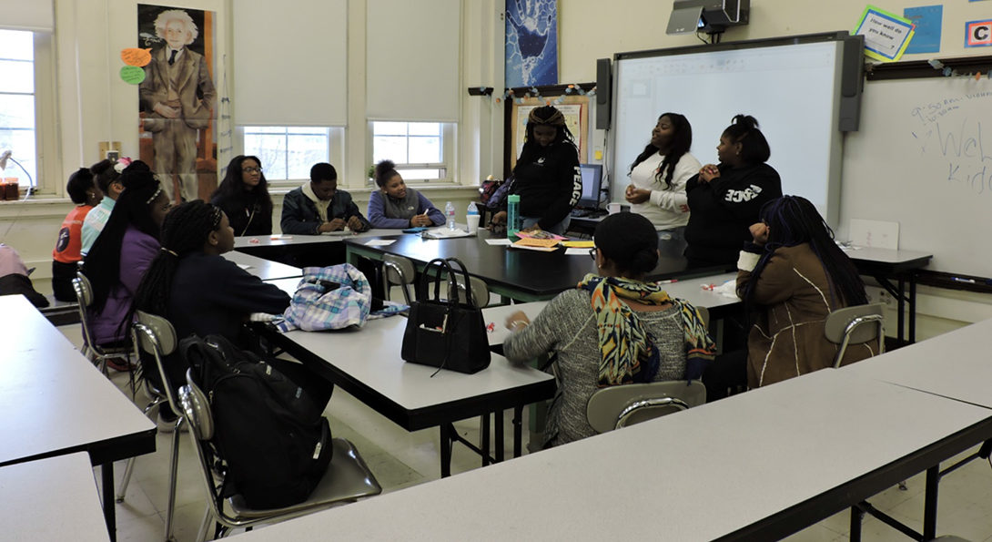 Three Black girls are leading a workshop on non-violent conflict resolution, with students sitting around three tables and listening, at North Lawndale College Prep.