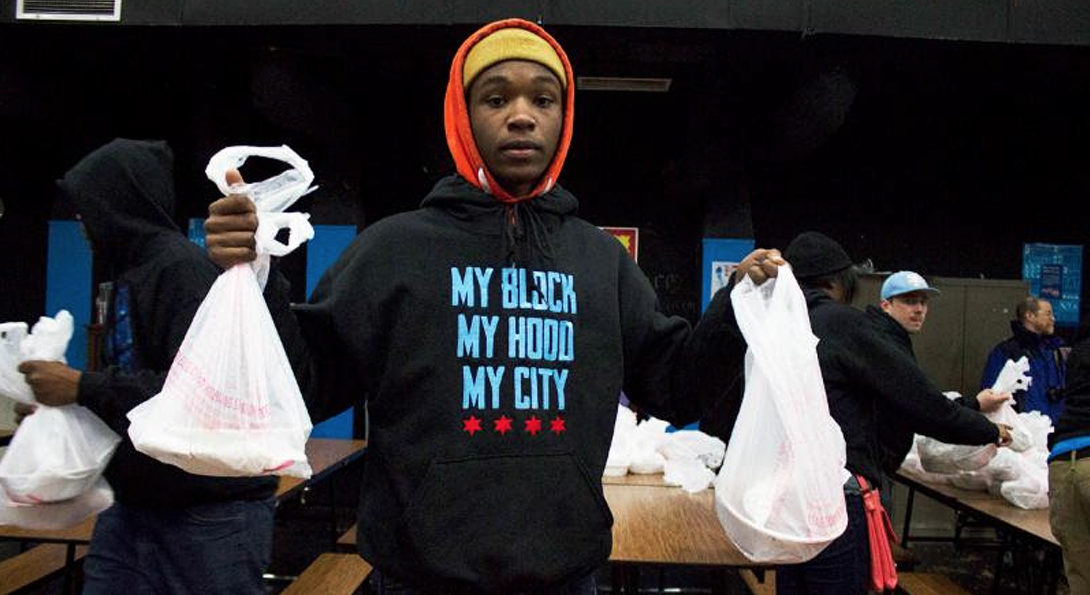A teen participating in a My Block My Hood My City activity carries bagged lunches at an event serving food to the homeless in Uptown.