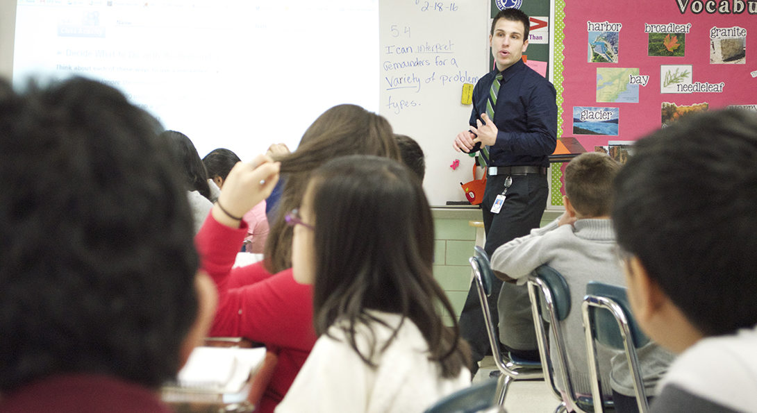 Teacher Michael Scaletta teaches a math lesson in his classroom at East Prairie Elementary in Skokie.  He is standing at the front of the room, walking in front of the whiteboard, while students are sitting at their desks, watching and listening.