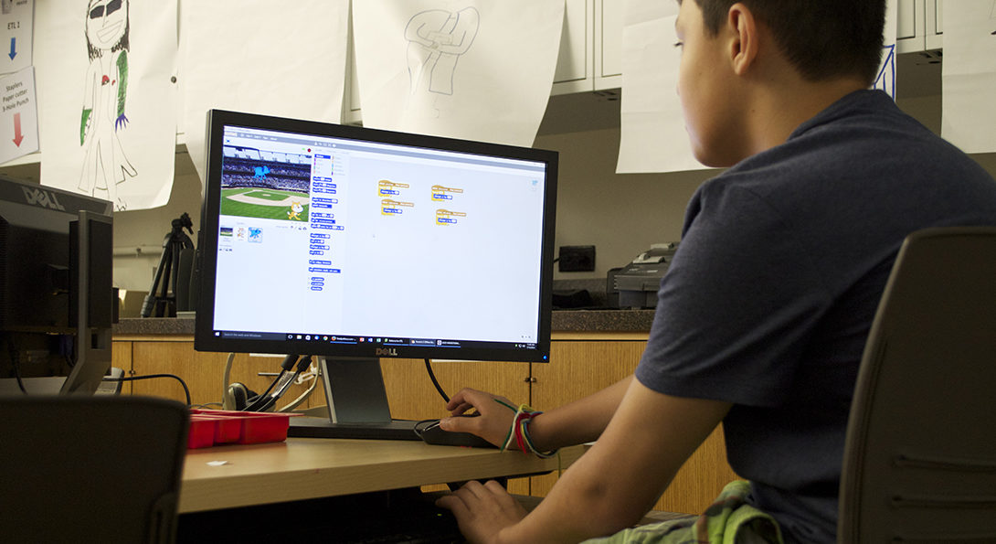 A Latino boy sits at a computer, engaged in a coding activity.  Lines of code are displayed in color on the computer screen in front of him.
