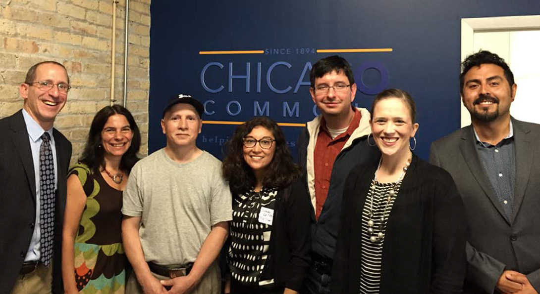 Members of the Chicago Commons Network pose for a photo, standing in front of a blue wall with the Chicago Commons logo on it.