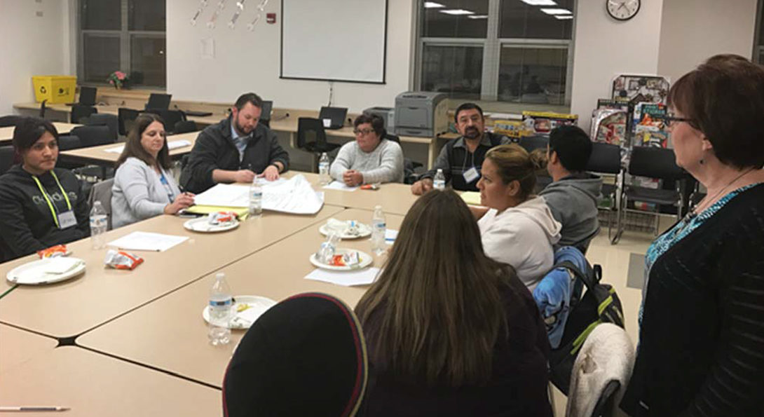 Parents from the Two Rivers Head Start Center sit around a table with Ernesto Reyna, learning about gardening and going over building plans for the future greenhouse.