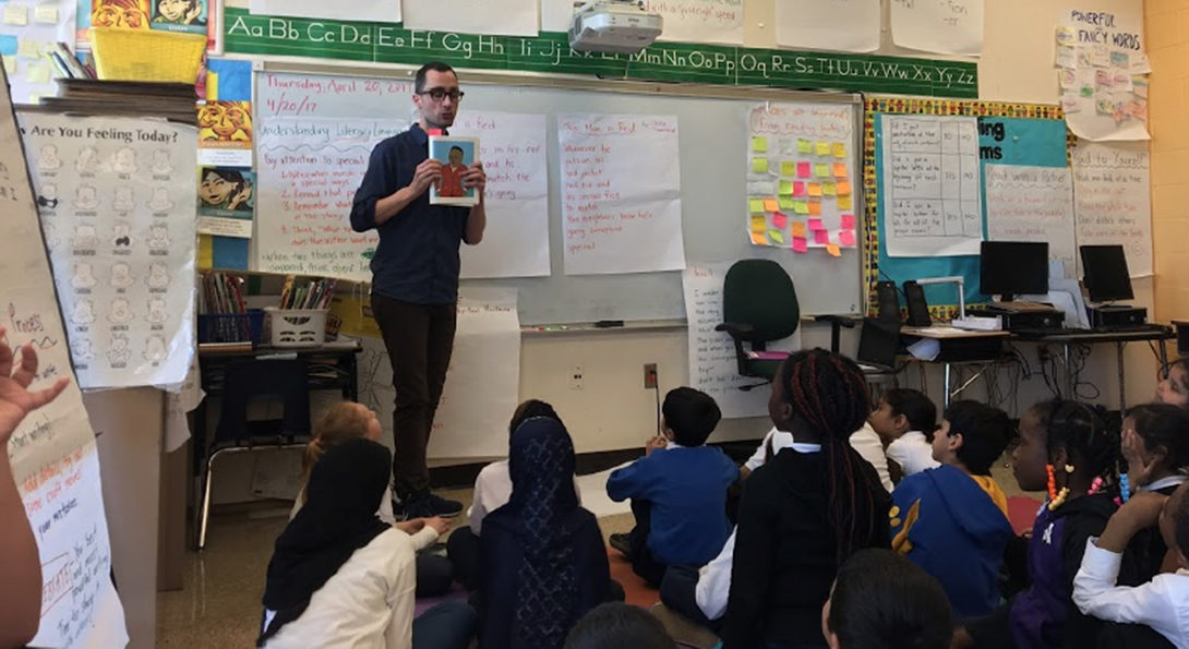 A teacher participating in Project SUSTAIN reads a book to his class.  He is standing at the front of the room, holding the book open and displayed to his students.  His students sit on the floor in a group, listening to the story.