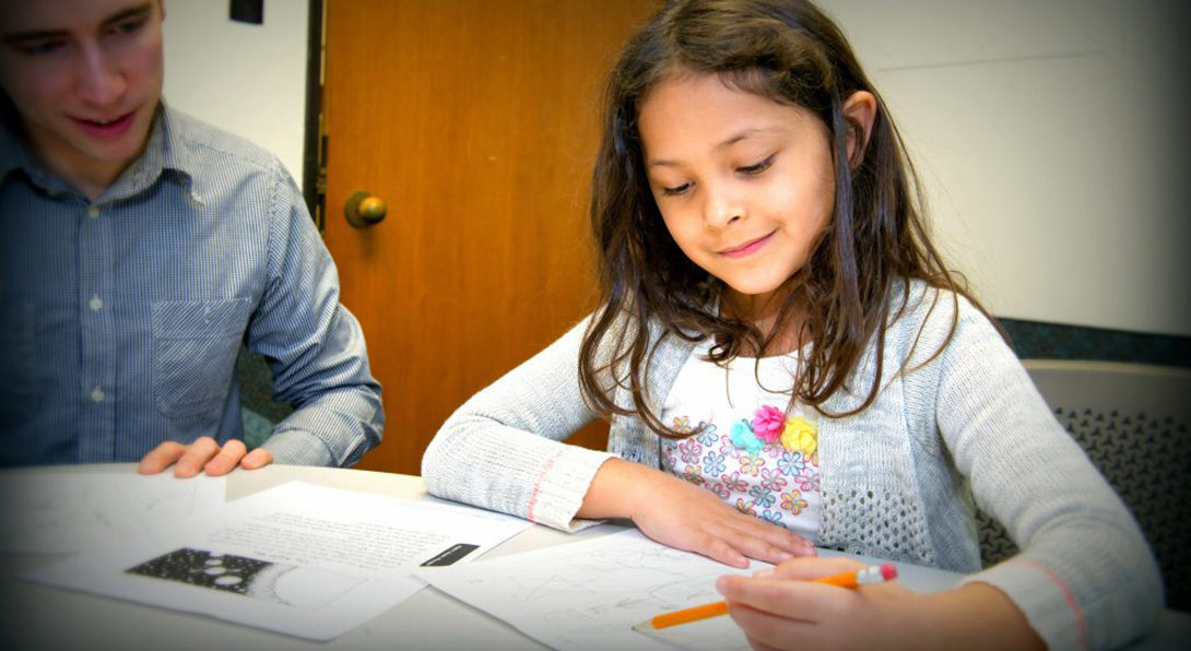 A girl undergoes an education assessment, working through a series of problems on a piece of paper while holding a pencil.  A Masters of Special Education student is sitting to her right observing her work.