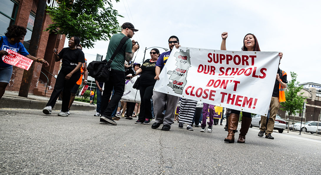 Parents and community activists march through a Chicago street carrying a banner that reads