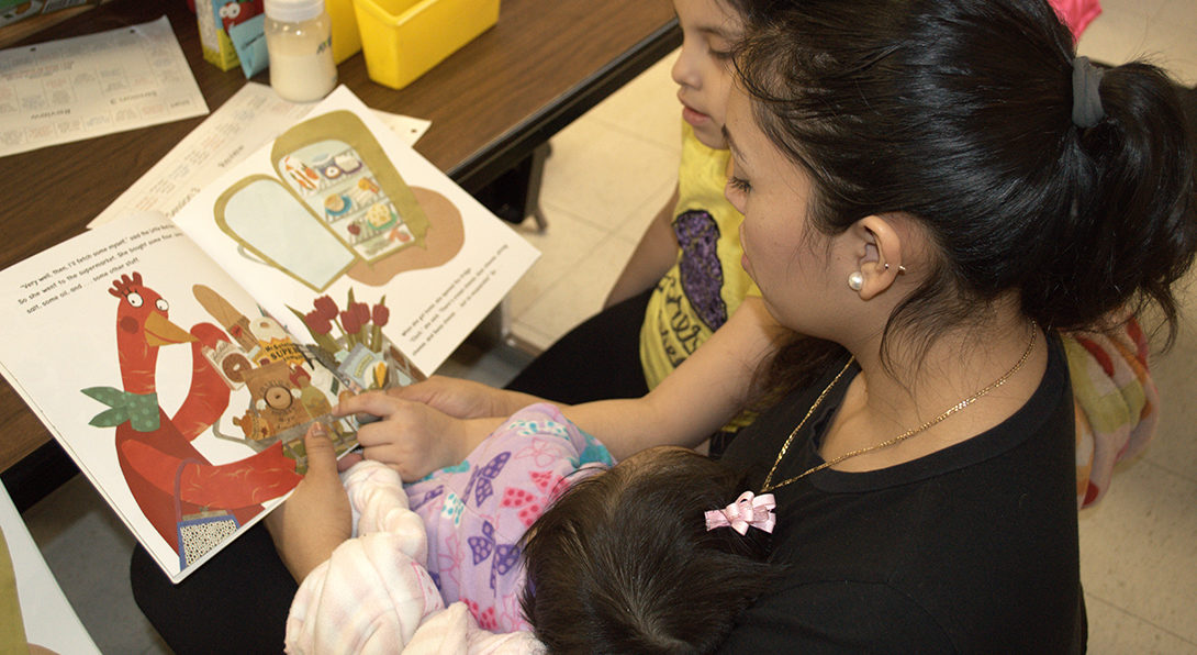 At a Center for Literacy workshop for ESL parents, a Latina woman reads a children's books to her two kids, who are both sitting in her lap.