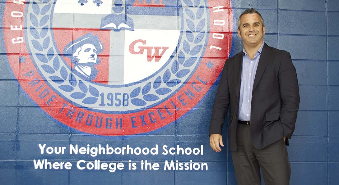 Principal Kevin Gallick poses for a photo in a hallway in George Washington High School, a CPS school on the far southeast side of the city.  Gallick is standing in front of a blue wall that has George Washington's red, white and gray logo painted on it.