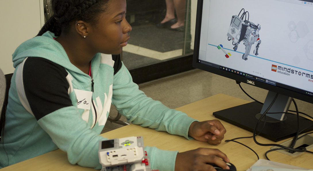 A Black girl sits at a computer, looking at the screen with her right hand on the mouse.  On the screen is an image of a robotic dog.  She is using a computer program to manipulate a physical robotic dog on the table in front of her.