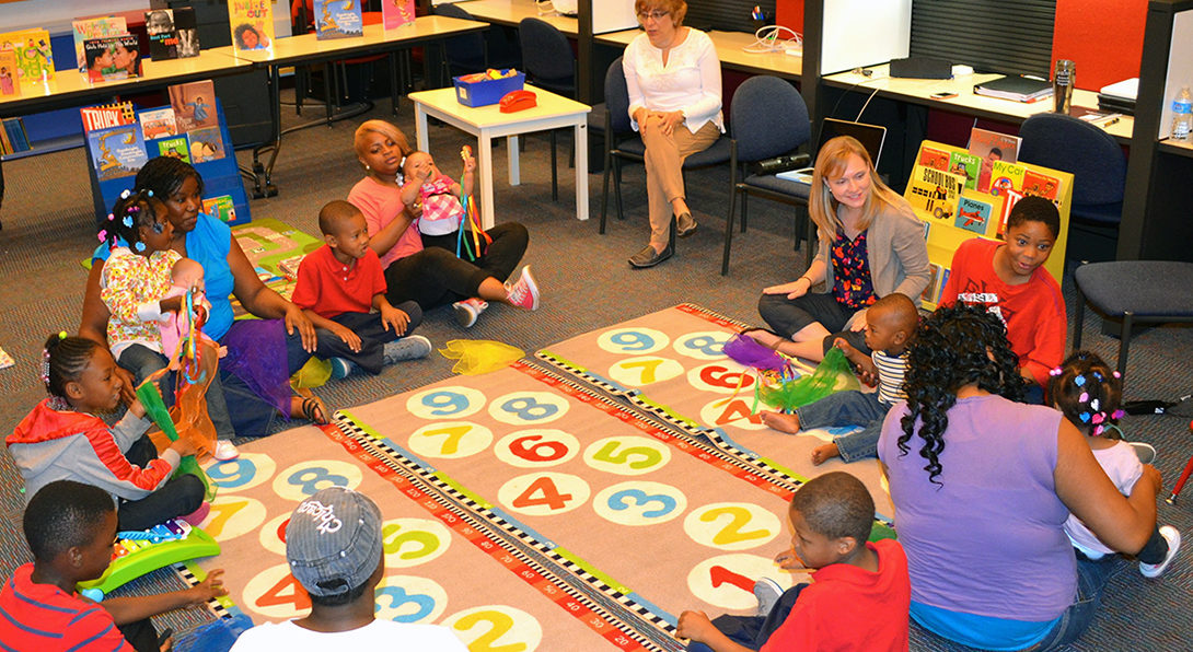 Doctoral student Colleen Whittingham leads a workshop with young mothers focused on developing literacy skills for early childhood learners.  The group is sitting in a circle on a colorful rug featuring numbers, and they are singing a song about counting.