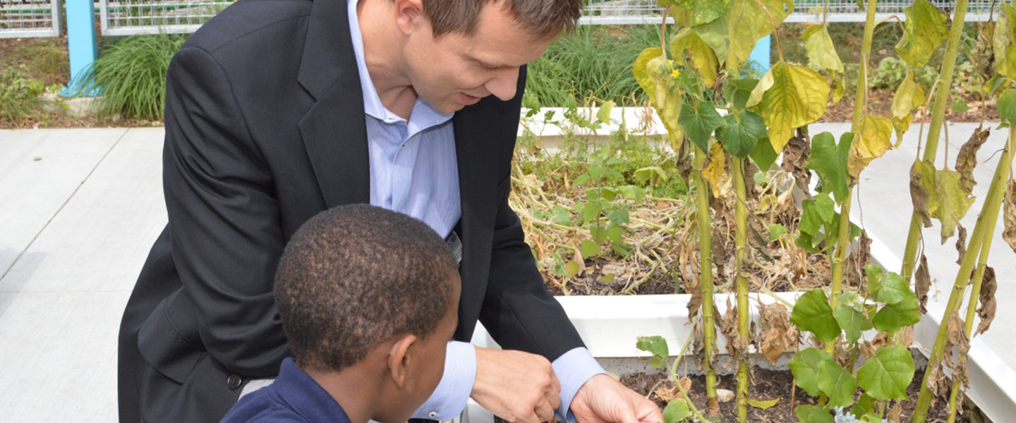 Principal Michael Beyer kneels next to a planter with a young student.  Beyer is holding up a leaf from the plant, showing it to the student.