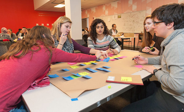 Students in the UIC Innovation Center work on a group project while sitting around a table.  They are using post-it notes to create a poster featuring a flow of information on it.