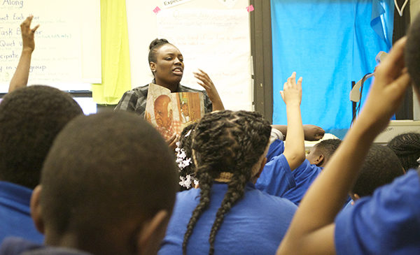 A teacher is reading a book to a group of Black students seated in front of her.  The teacher is gesturing with her left hand while asking a question while displaying the book to her students.