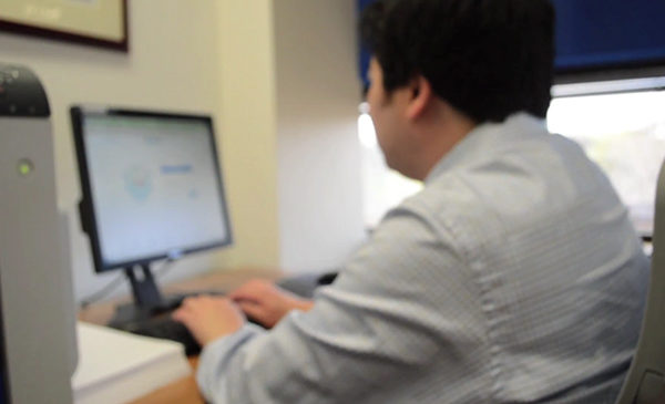 A researcher sits at a computer, entering in data to a spreadsheet by typing on a keyboard.