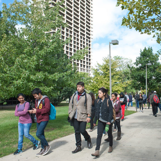 UIC students walk down a sidewalk on east campus towards Harrison Ave., with trees and University Hall in the background.