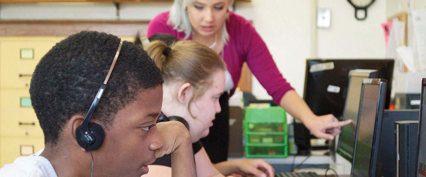 Special education teacher Samantha Rosell gestures at a computer, while a female student is sitting in front of her looking at the computer.  In the foreground, a Black student wears headphones and is looking at a computer screen.