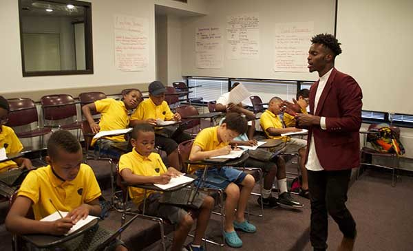 A Black male teacher walks at the front of a classroom, talking to the boys sitting at desks to his left in his class.