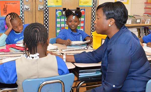 Principal Peggie Burnett sits at a desk next to three students, discussing with them what they are working on in their class.