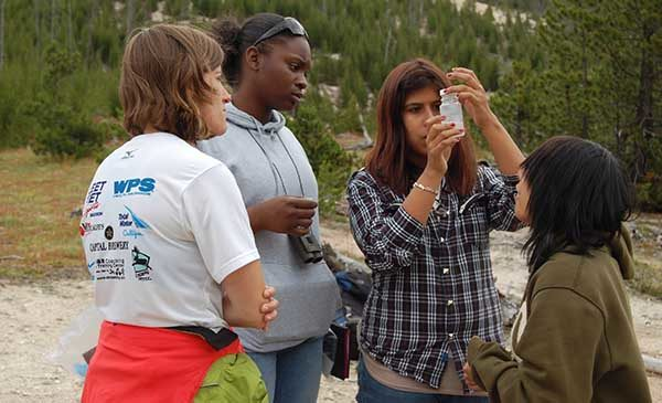 A group of girls stand near a body of water in a forest.  One of the girls is holding up a plastic vial, and all the girls are looking at the water in the vial.