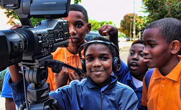 Four boys stand behind a video camera.  One is wearing headphones, while the other three are looking at and discussing the footage on the camera screen.