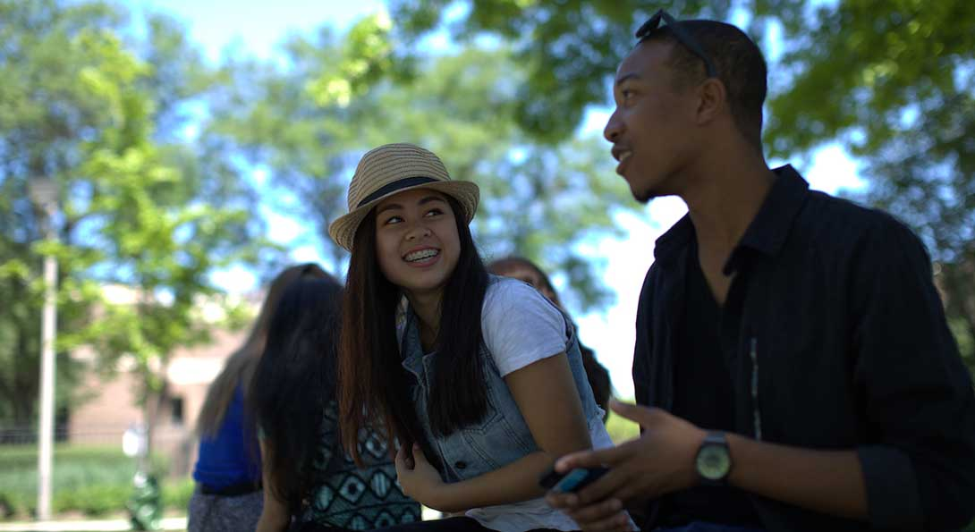 Students sit on a bench under a tree on campus, having a conversation.