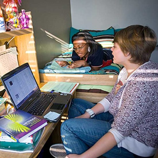A student sits at her desk in a dorm room, looking at her computer, talking to a girl laying on a bed to her right.