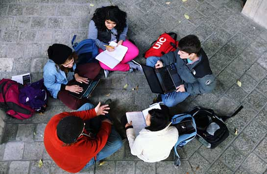 Five UIC students sit in a circle, talking and typing on laptops.  They are on the patio atop the BSB building on UIC's campus.