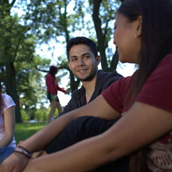 Students sit on the ground on UIC's campus socializing, while another student walks by in the distance.