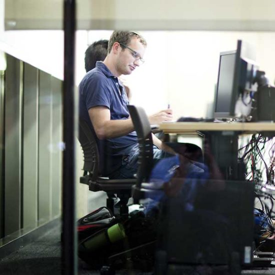 A student sits at a computer in a computer lab on campus, writing on a piece of paper and looking at his computer screen.