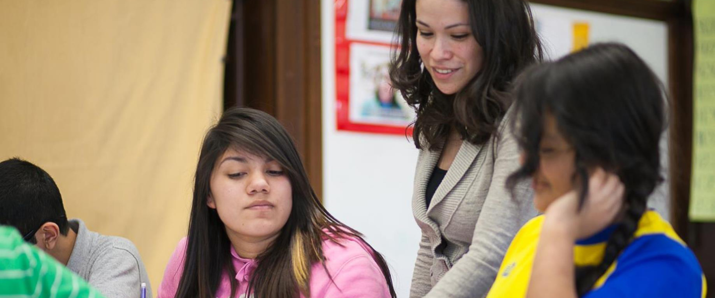 Teacher Jasmine Juarez stands behind two girls who she is talking with, gesturing at a piece of paper on one of the girl's desk.
