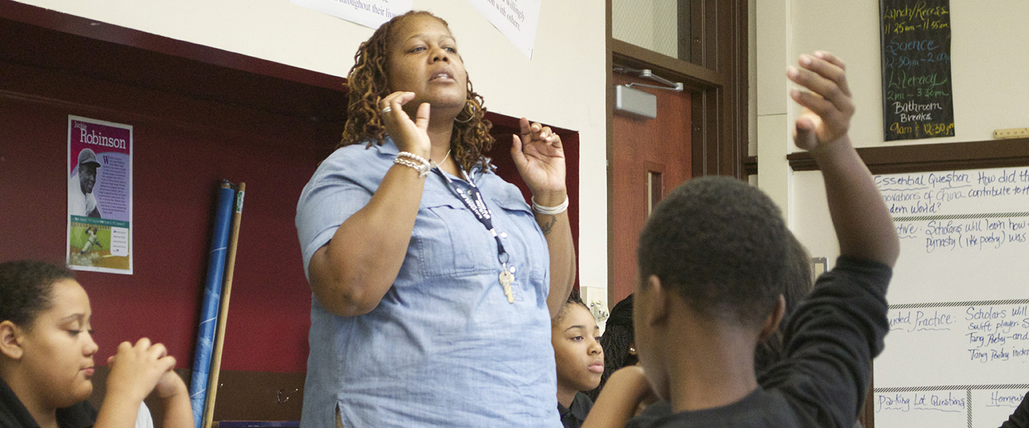 Teacher Tonja Robinson-Harris leads a discussion in her classroom.  She is standing near a wall with both hands raised to make a point.  In the foreground, a Black male student has his hand raised to answer a question.