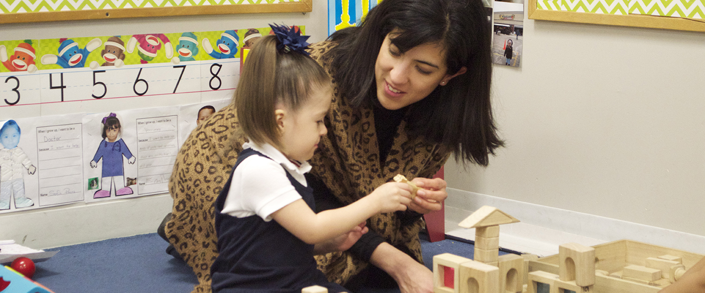 Giselle Nunez kneels on the ground next to a young girl and is handing her a block.  The girl is building a block tower.