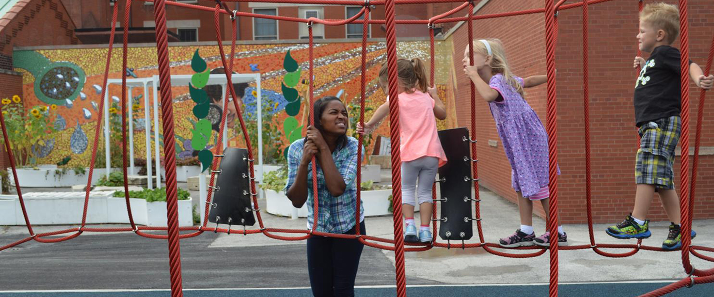 Early childhood education teacher Star McFarlane is standing next to a red rope bridge on a playground, holding one of the rope supports.  She is smiling at three children, who are making their way from right to left across the rope bridge.