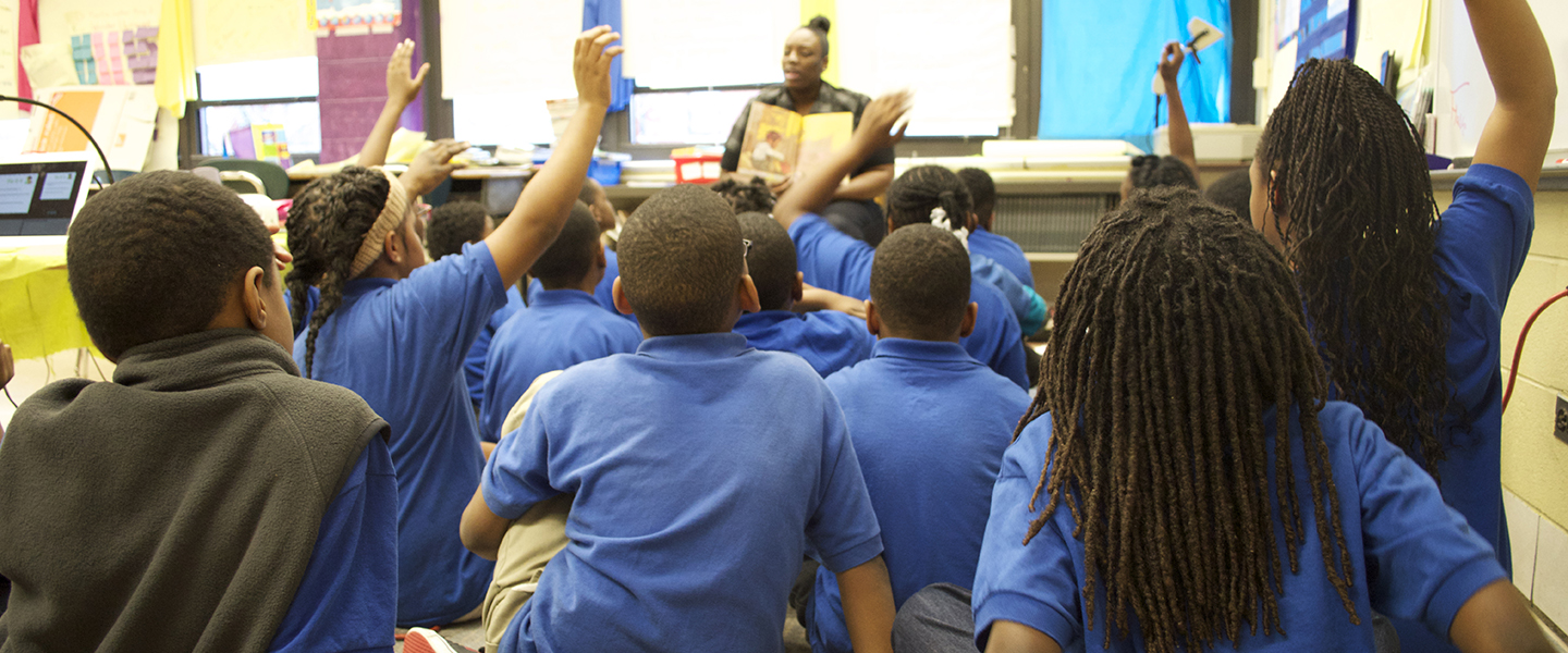 Teacher Carmen Washington sits in a chair reading a book to a group of students seated on the ground in front of her.  A number of students have their hands raised in response to a question she has asked.