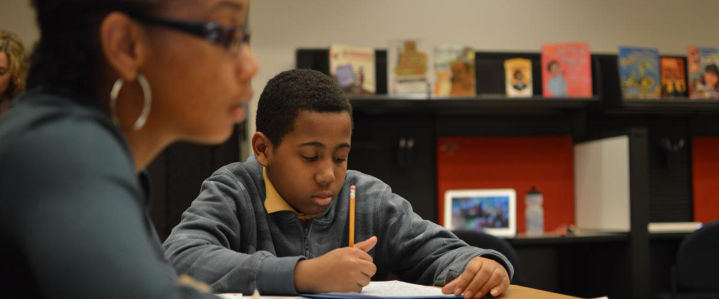 A Black male student is writing with a pencil sitting at a table in the UIC Reading Clinic.  To his right in the foreground, a Black female student is reading a book.