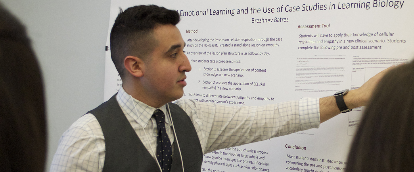 Student Brezhnev Batres presents his research to other students.  He is standing in front of a large poster, gesturing at it with his left hand and explaining its contents to two female students in front of him.