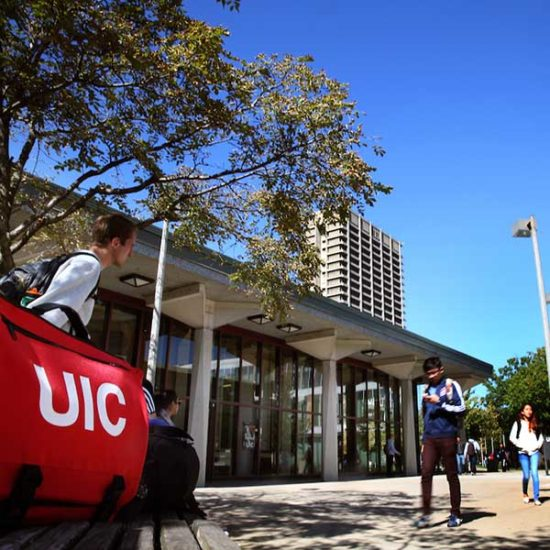 Students walk by a lecture hall along the quad of UIC's campus, with University Hall in the background.