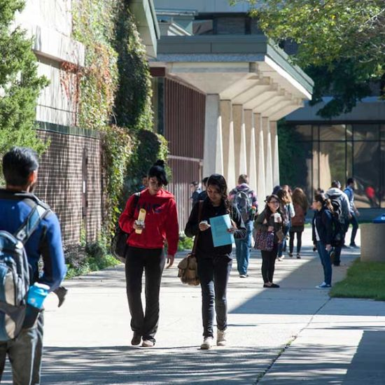 Two female students walk across the UIC quad past a lecture hall.  One student is looking at her phone while walking.  Other students are walking in the other direction in the background.