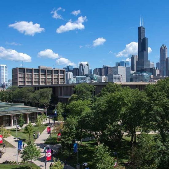An aerial view of UIC's campus, with a sunny day and the Chicago skyline in the background.