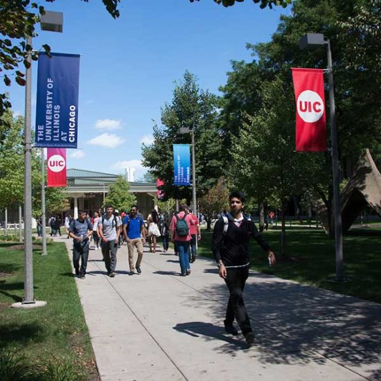 Students walk across a sidewalk away from the UIC quad and lecture halls.
